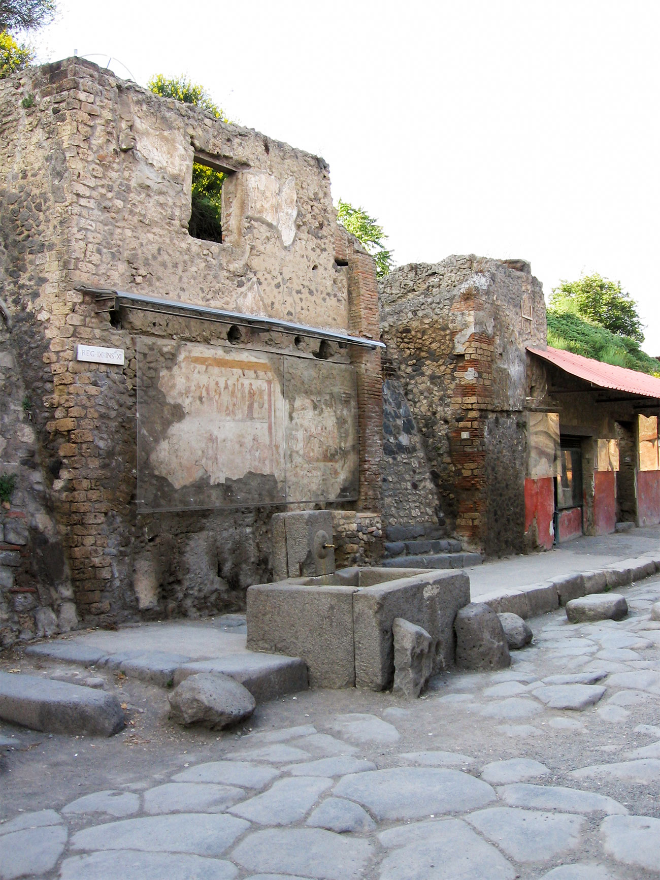 Vertical color photo of ruins from a street in ancient Pompeii showing different types of structures side by side