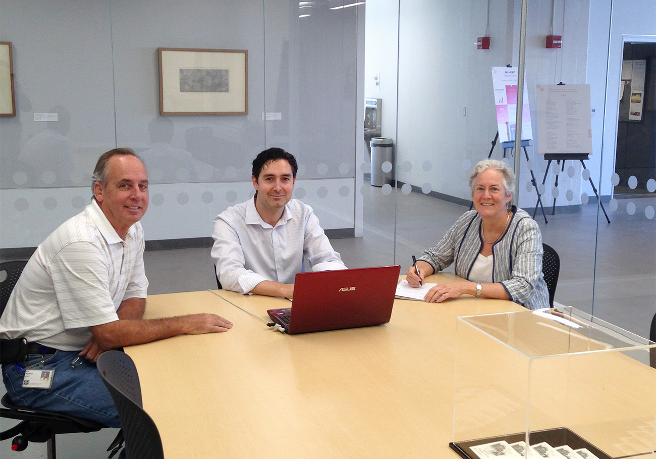 Two men and one woman sit in a glass-walled conference room