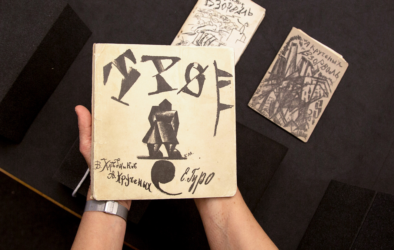 A woman's hands holding a square book whose cover features a constructivist figure and a large upside-down comma