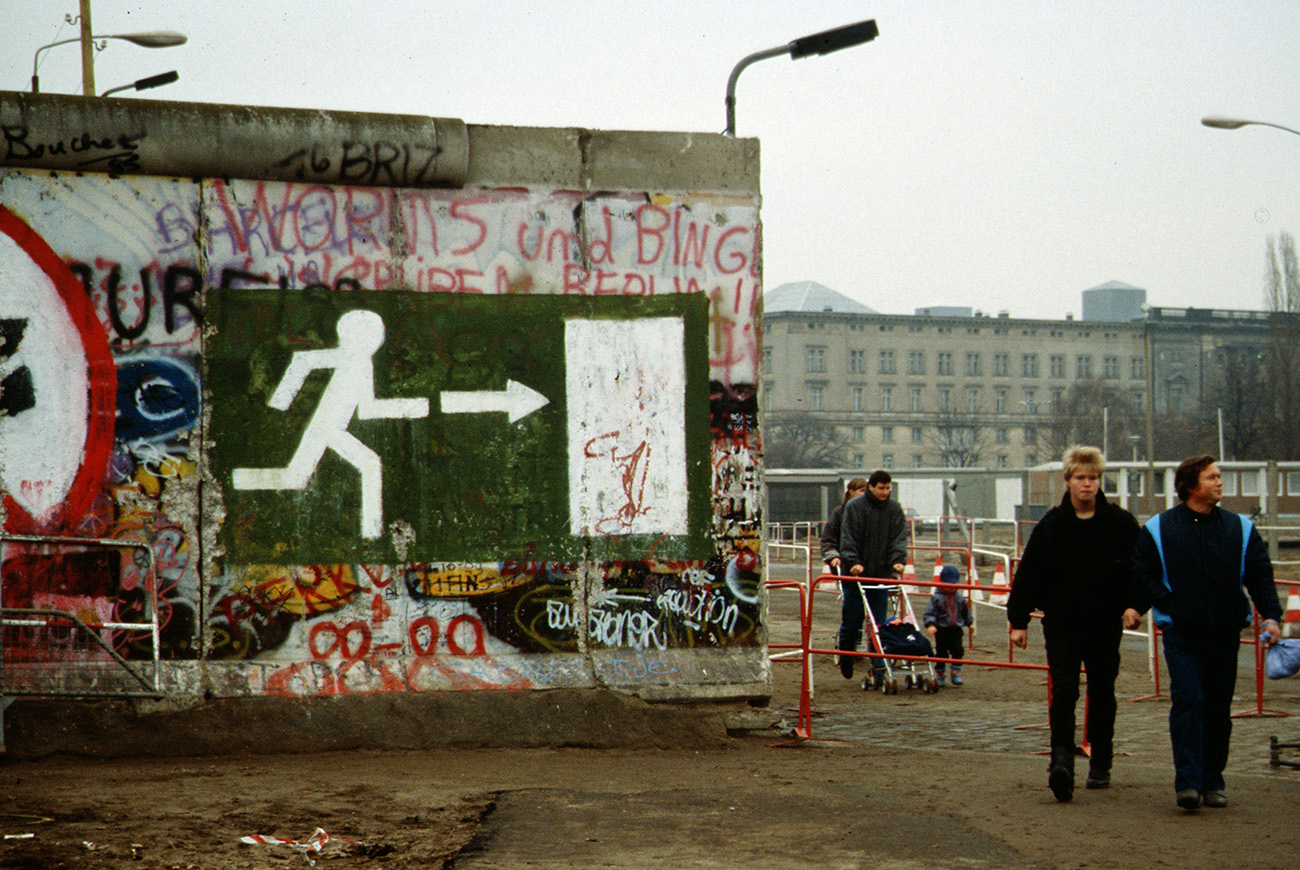 A couple walks next to a fragment of the Berlin Wall after it had been dismantled.