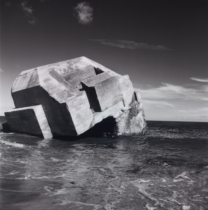 Black and white photo of a large concrete block sinking into the sea