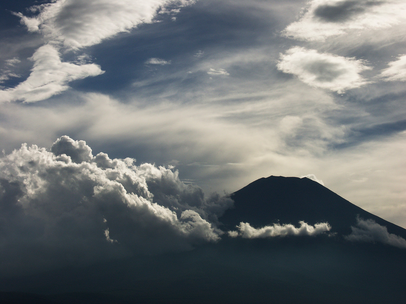 Color photo of Mount Fuji partially obscured by dramatic clouds