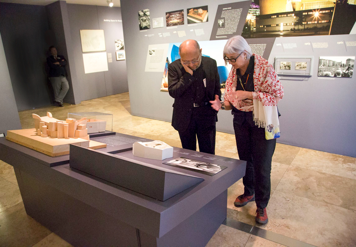 A man and a woman stand talking inside a gallery of architectural models and sketches