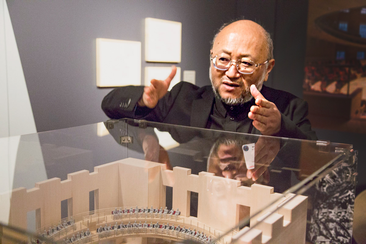 A Japanese man in glasses gestures while standing behind a display case for an architectural model