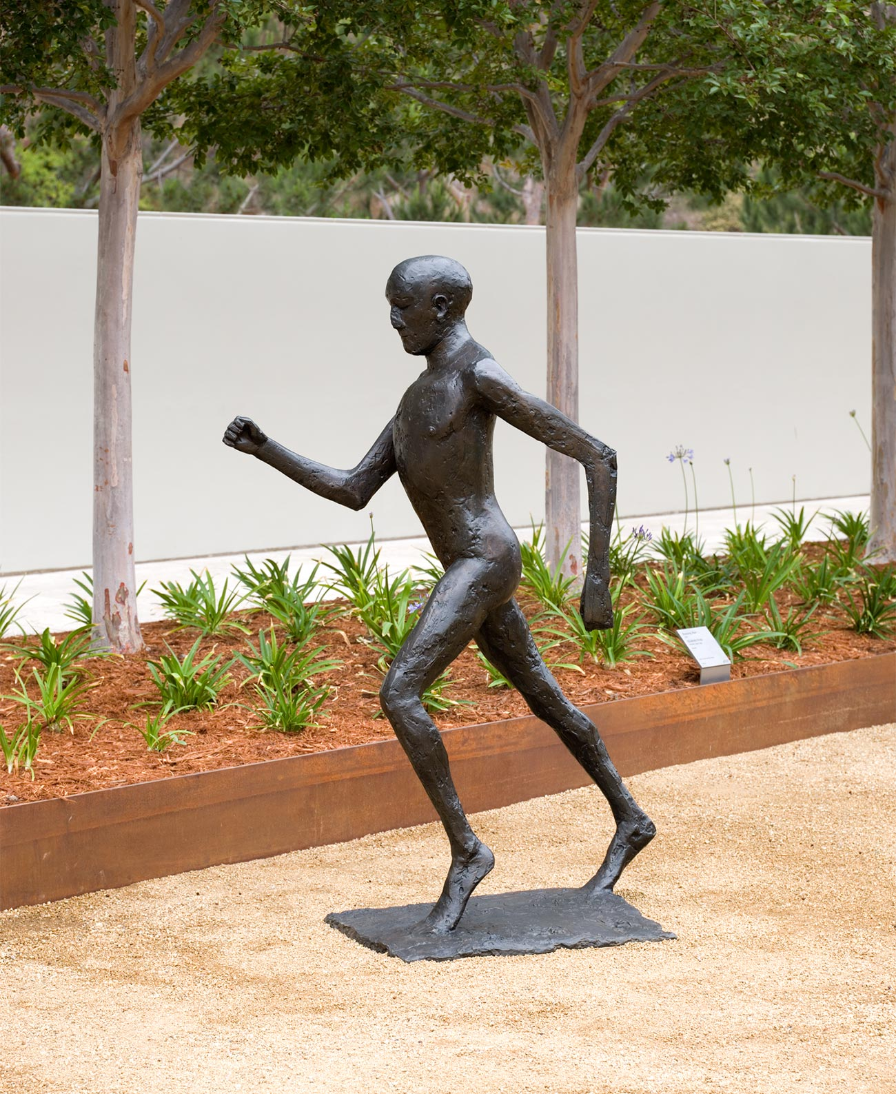 Side view of a nearly life-size bronze statue of a man in mid-stride