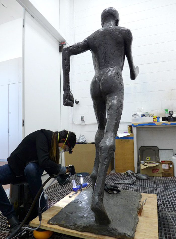 A woman in safety equipment works on the foot of a bronze, nearly life-size statue of a man running in mid-stride