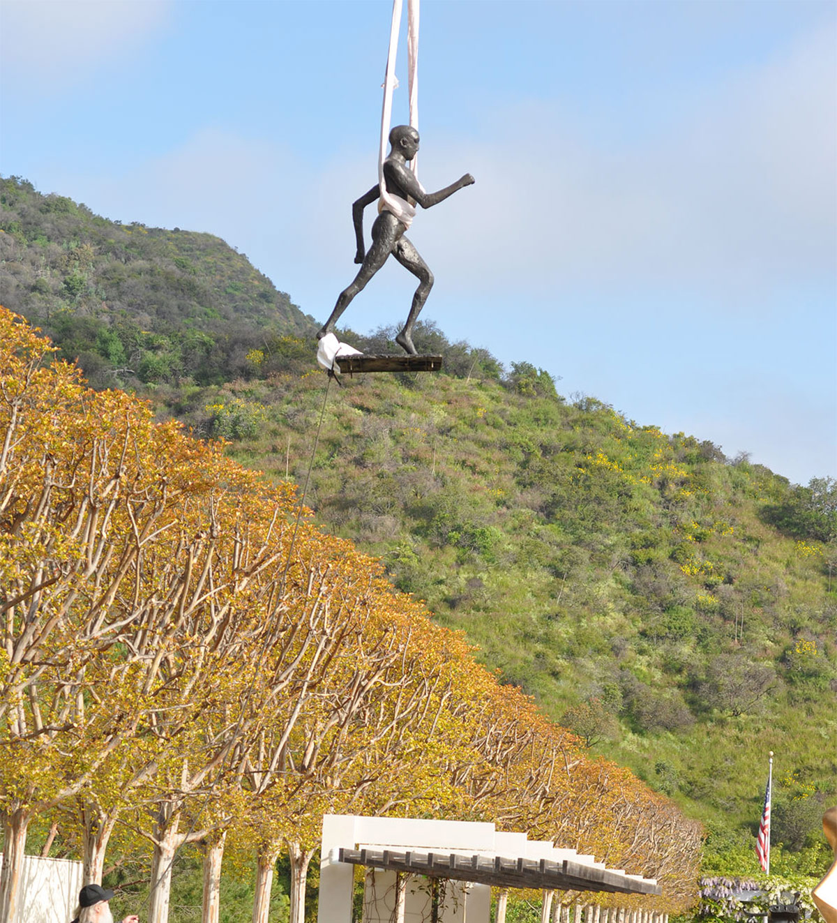A bronze statue of a running man hangs from an aerial crane, attached by white fabric straps