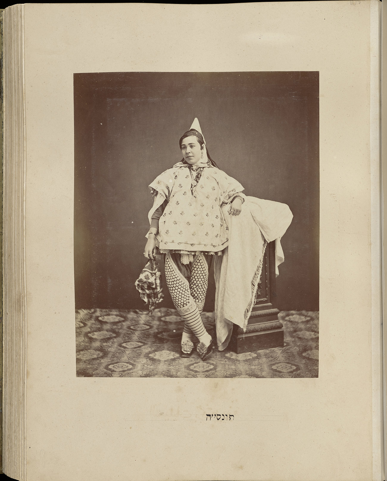Sepia-toned historic photograph showing a standing woman in ornate leggings and a pointed cap. She looks away from the camera and has her ankles crossed