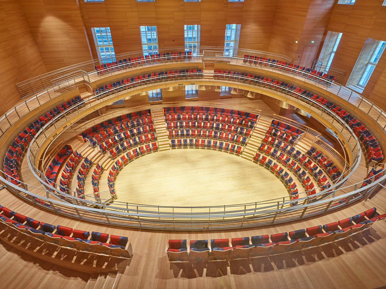 Interior view of a circular concert hall with a central stage and wood walls, floors, and seats