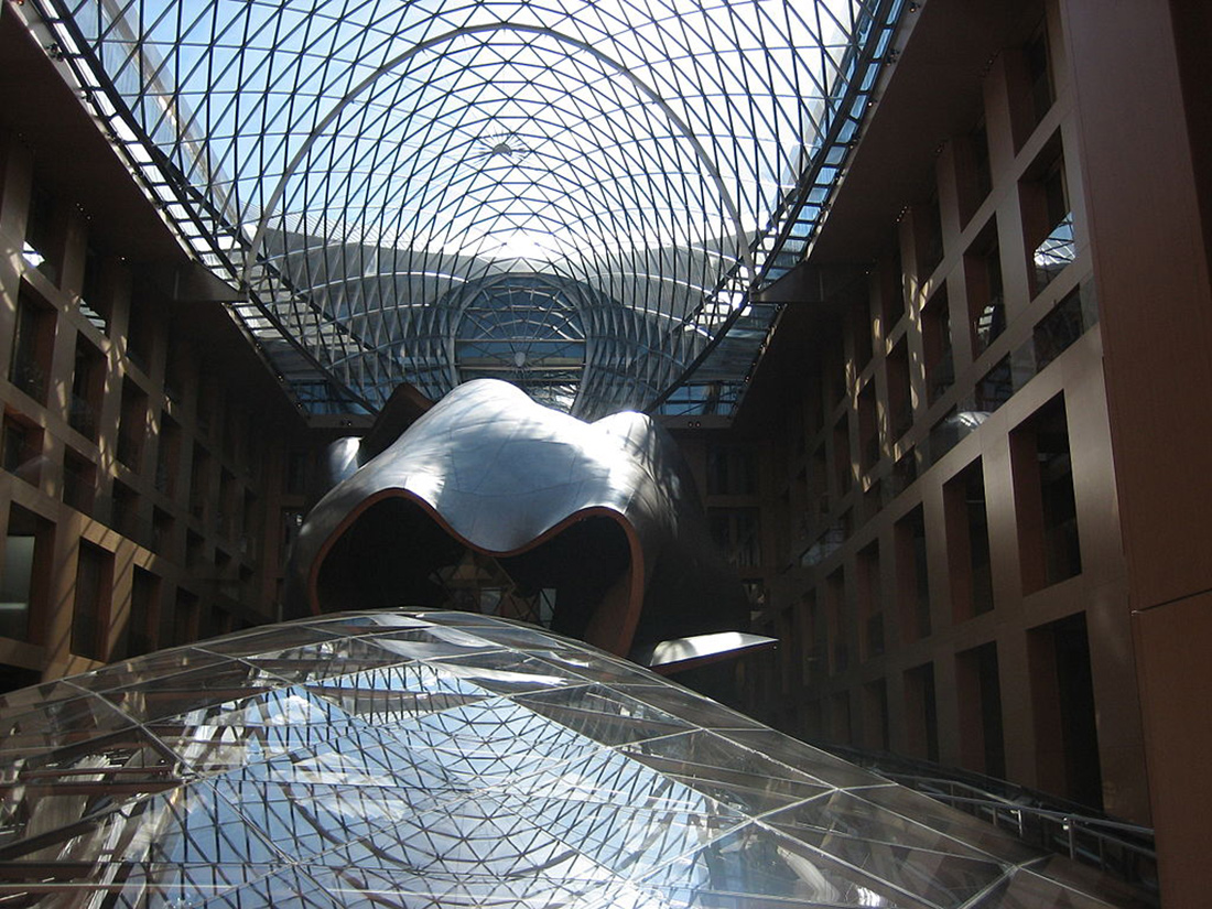 Low-angle view of undulating glass forms on the interior of a corporate building