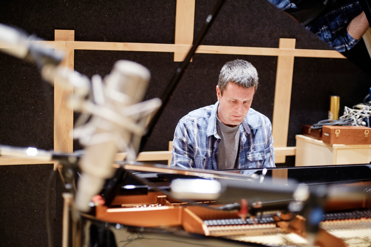 A man in a t-shirt and button-down blue shirt sits at a piano, composing music