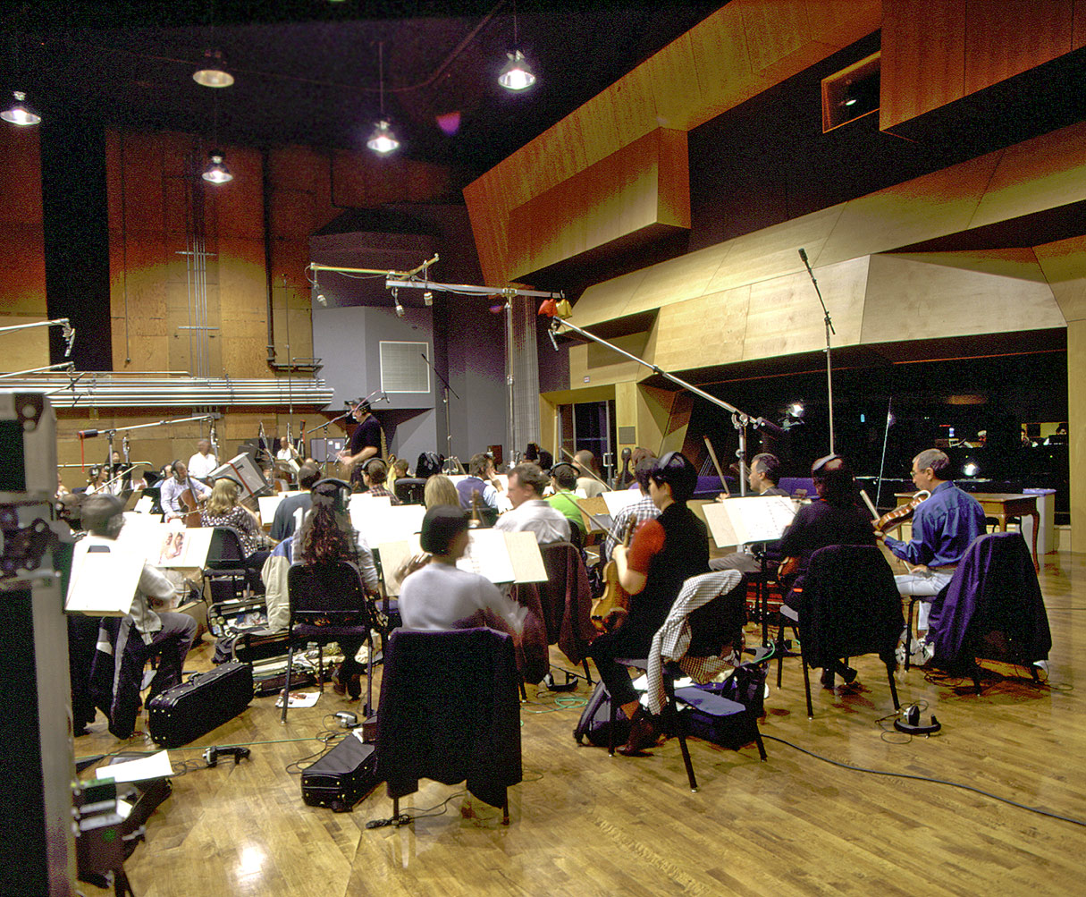 Orchesta members sit with their instruments in a wood-lined scoring studio