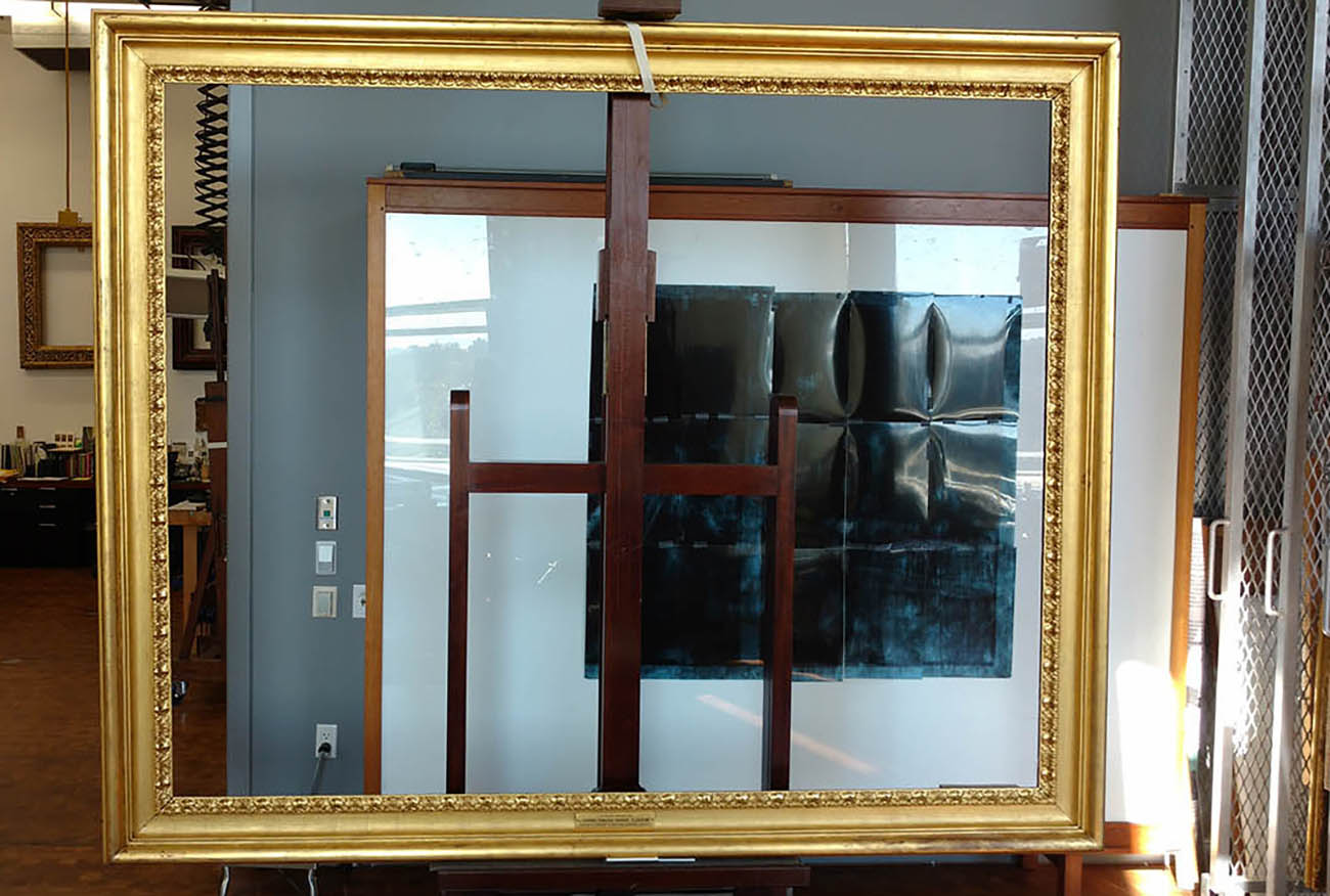 The image contains the frame on a wooden stand, freshly cleaned.