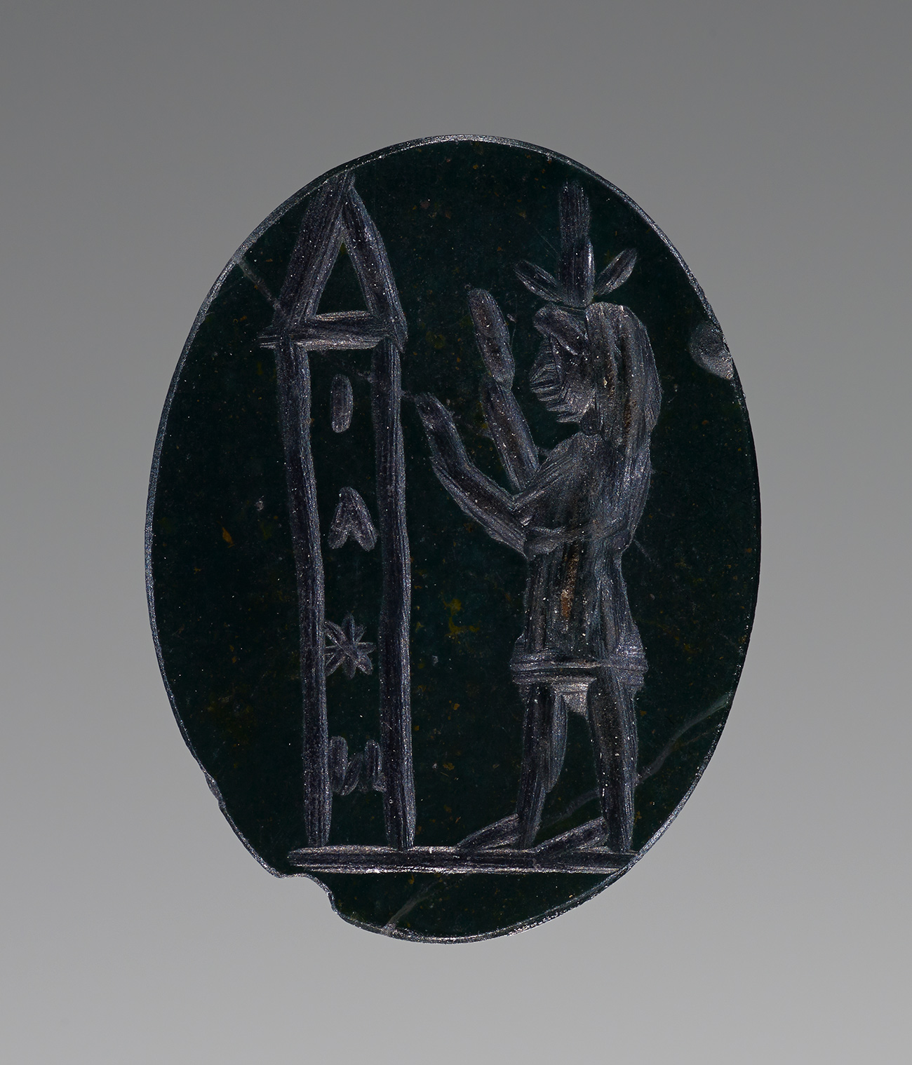 Closeup image of a dark blue carved gem. Engraved on the gem is a representation of a obelisk at left, and a subject at right with raised hands towards the obelisk.