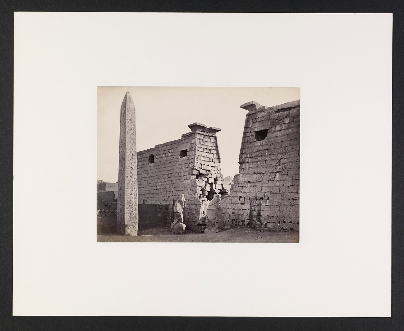 Black and white photograph with an obelisk at left and a wall running along the right side of the frame.