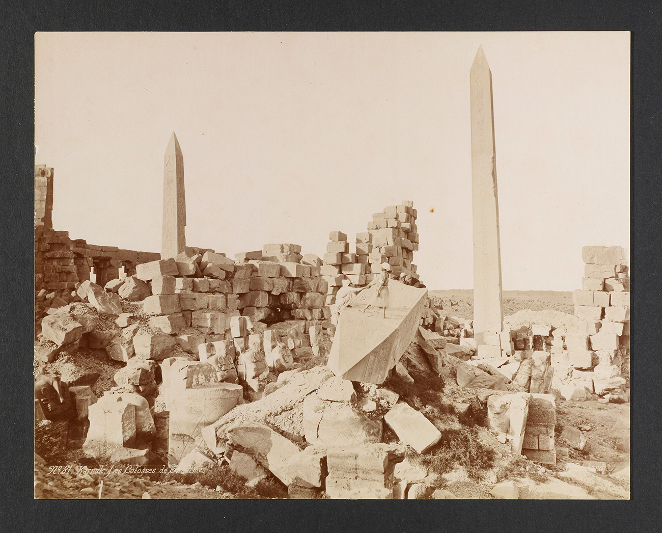 Sepia-toned photograph with two obelisks; fallen blocks are scattered in the foreground and background of the landscape.