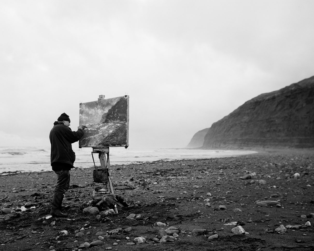 At left is a man, bundled up, painting a landscape on the shore of the beach.
