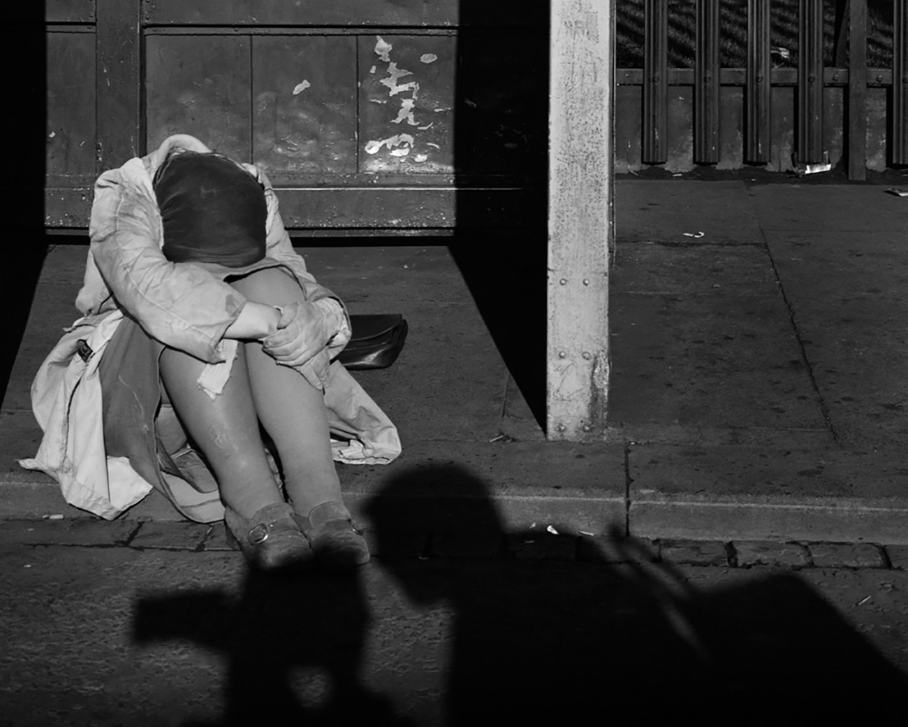 The image depicts a woman sitting on the curb, hugging her knees.