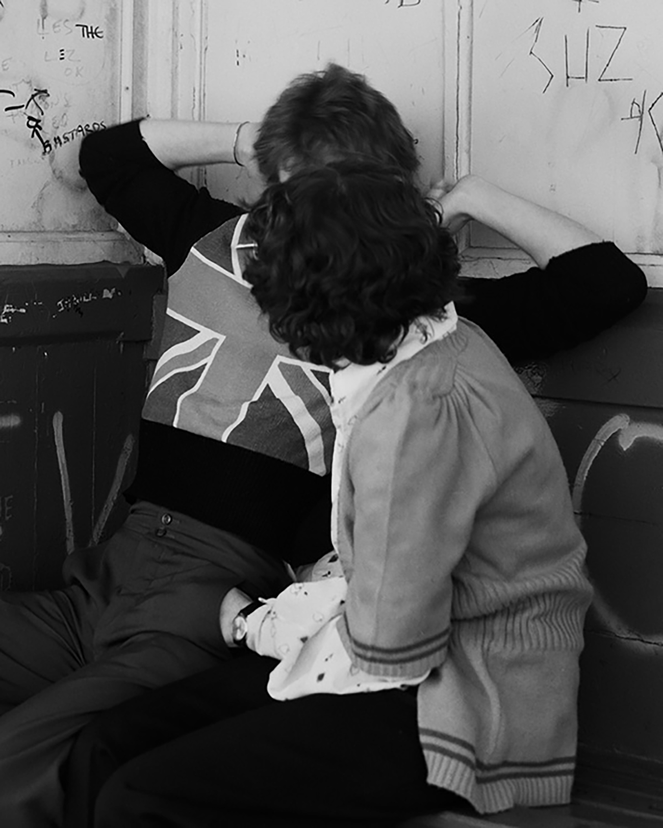 The image's fram is almost completely taken up by the two bodies of a couple. One of which, we can only see their back, as they are turned towards their partner, covering up the face of their partner as well.