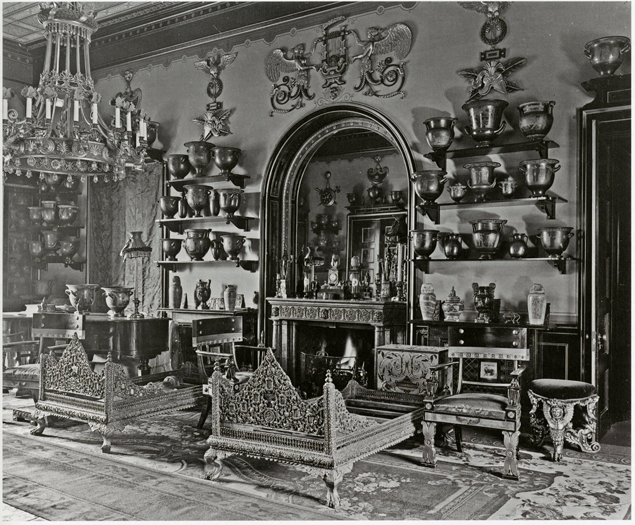 Black and white photo of an ornate Victorian interior with four rows of ancient Greek vases decorating the walls