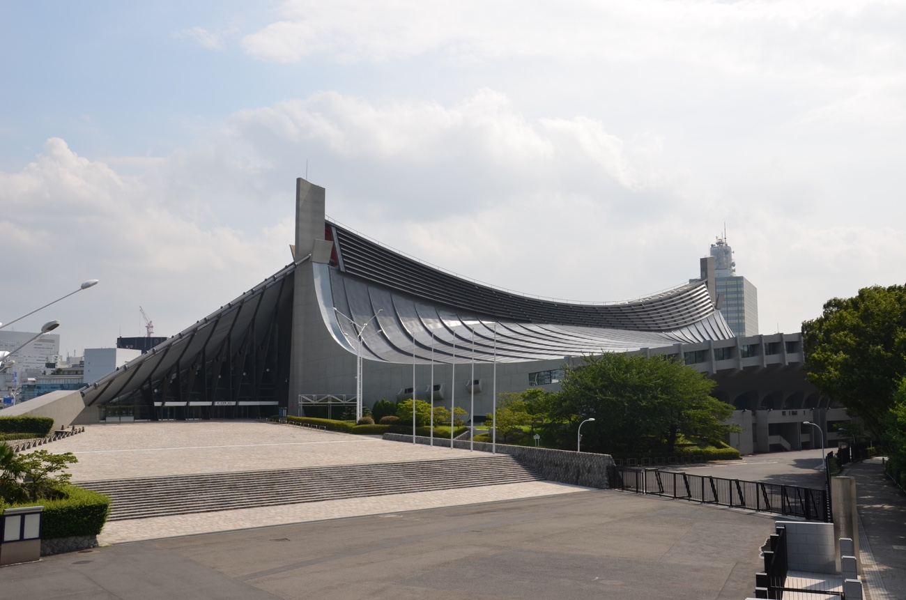 Wide-angle exterior view of a Japanese sports stadium with a pagoda-like suspended roof