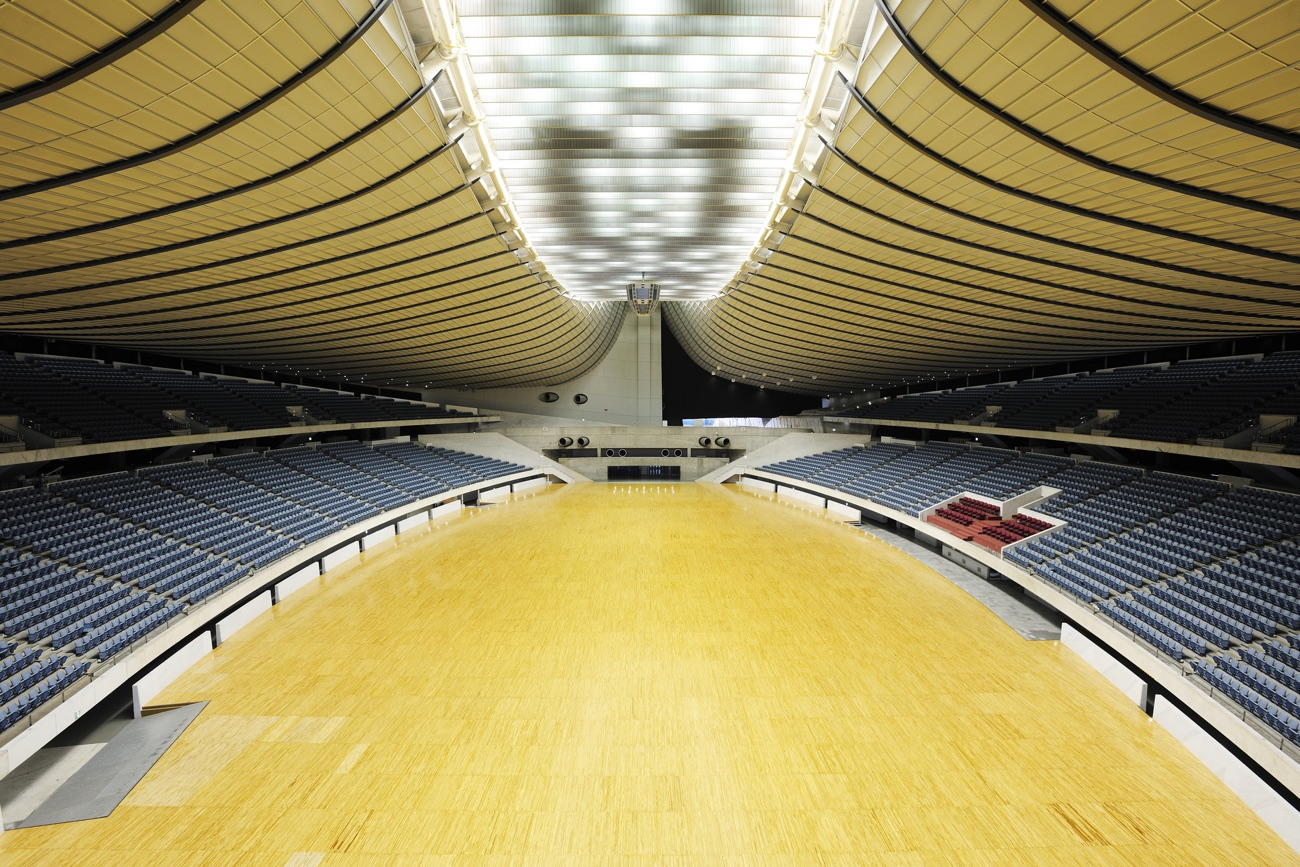 Interior view of a vast, oval, empty sports arena with vast expanses of wood on the floor and ceiling