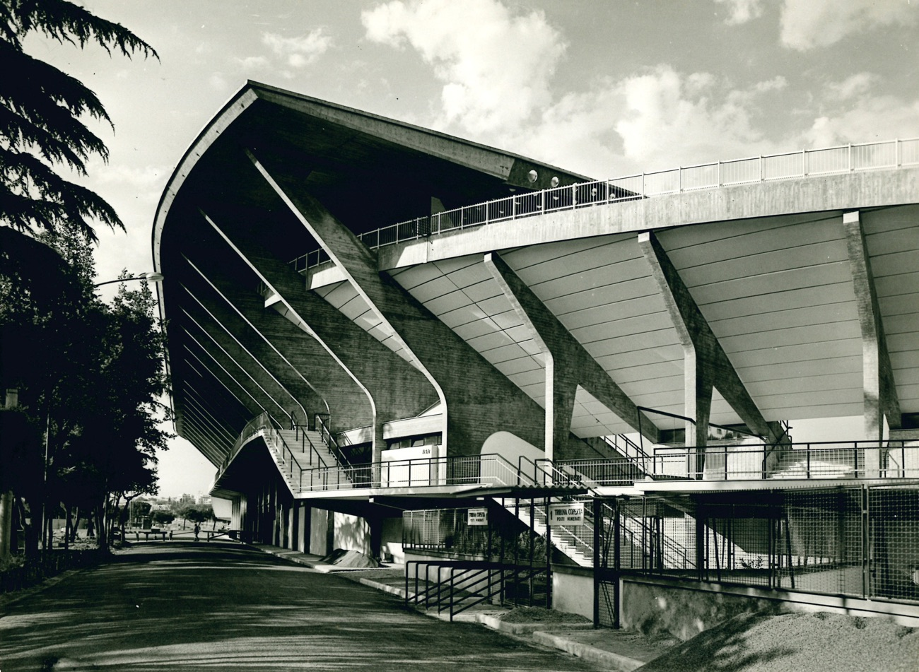 Black and white photograph showing the dramatic external concrete curvature of the Flaminio Stadium