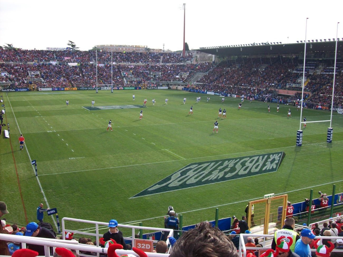 Overhead view of a rugby match in progress in a large open-air stadium