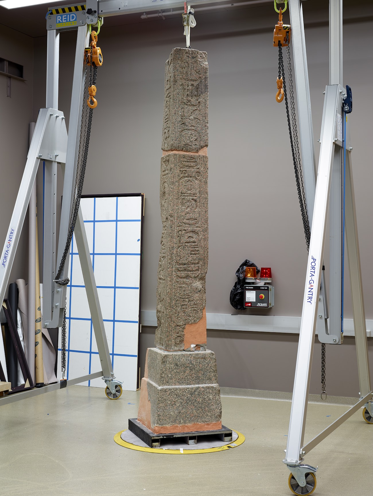 A large pink-brown obelisk stands in a conservation lab, held up by conservation rigging