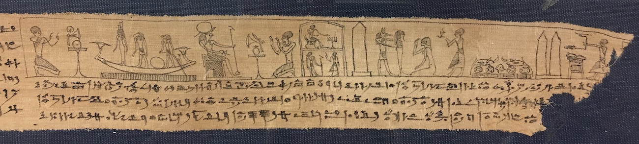 Detail of an unfolded mummy wrapping with Egyptian figures and an obelisk