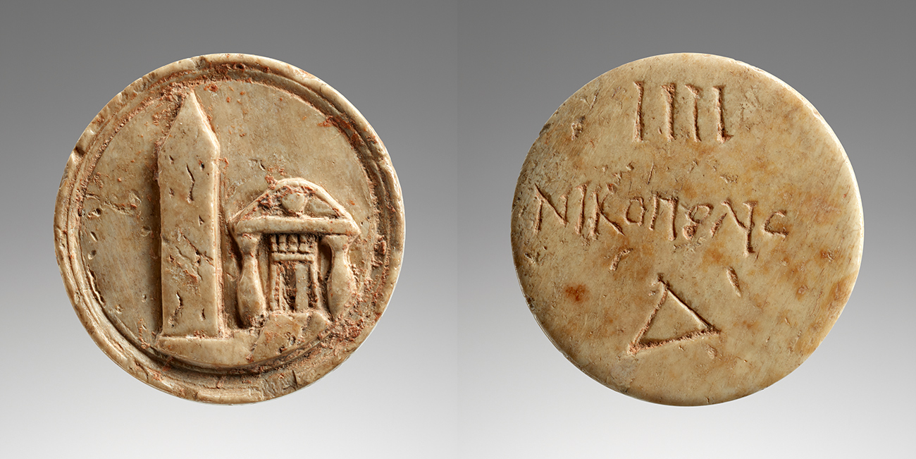 Front and back of a round, aged ivory token showing an obelisk and writing in Greek