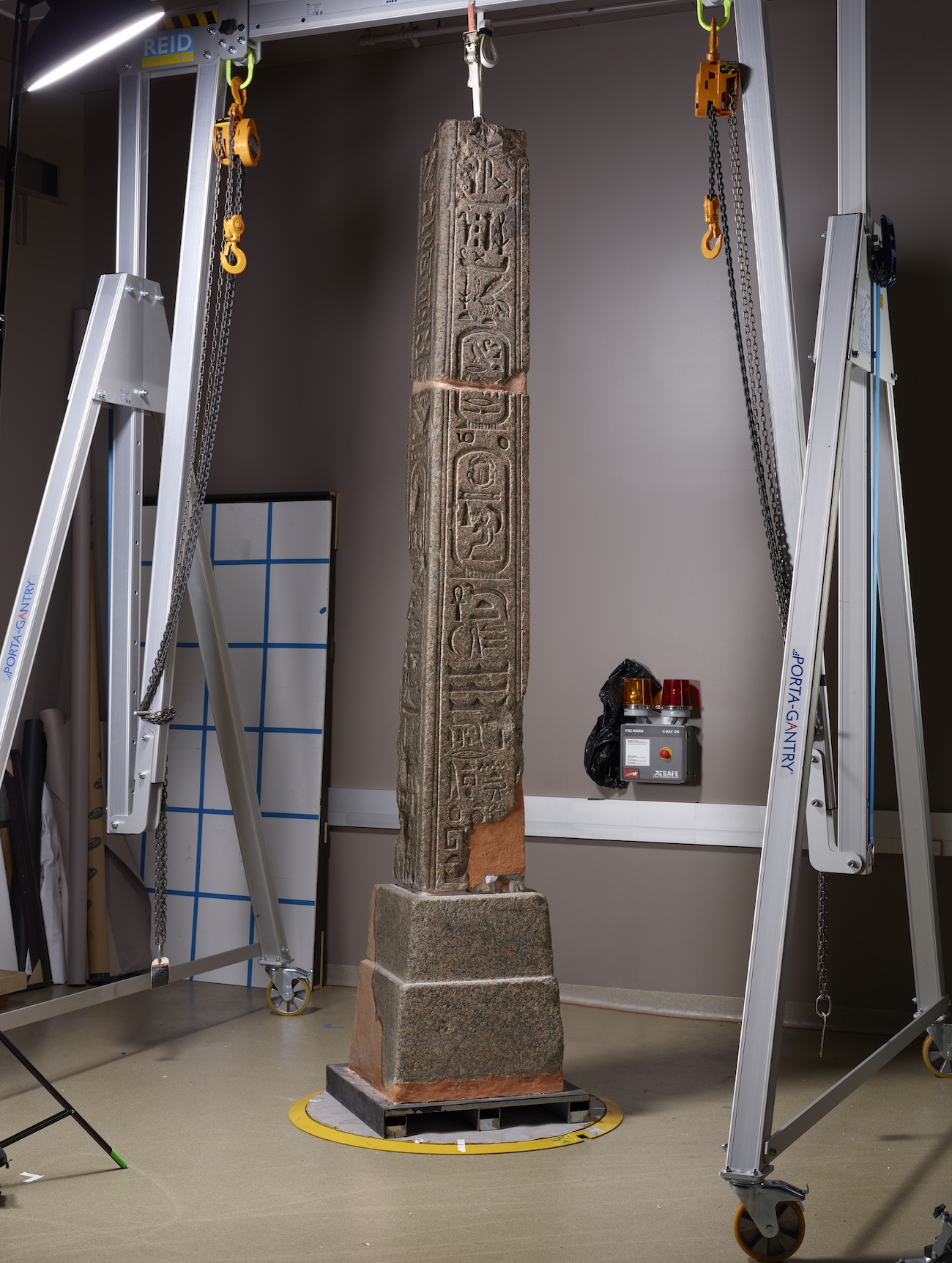 Egyptian obelisk in a conservation studio, illuminated by raking (side) light