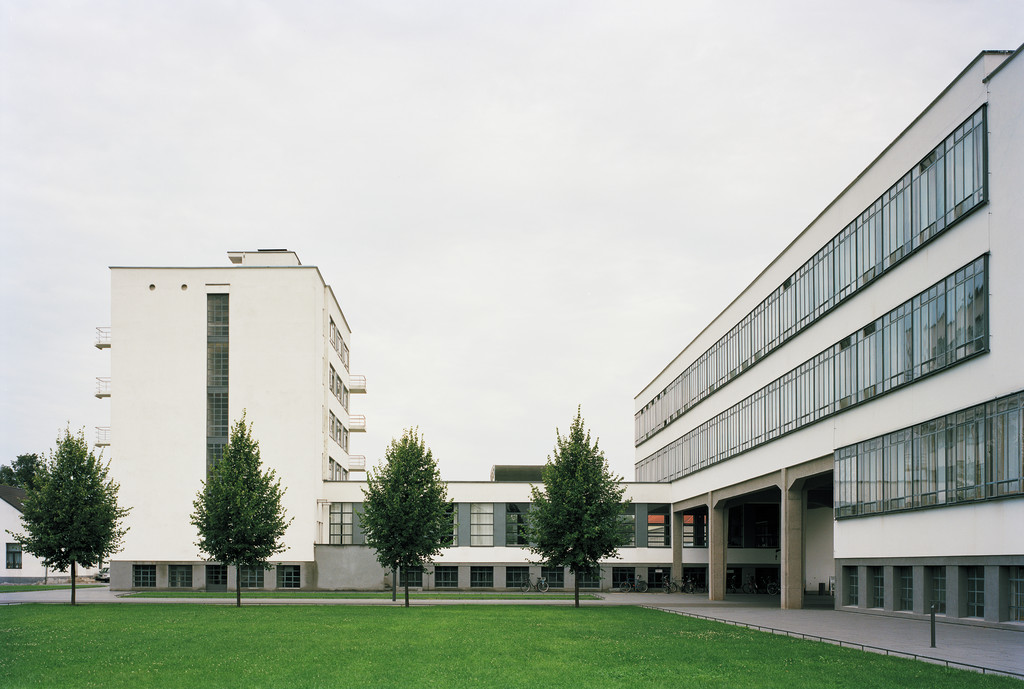 The white and glass exterior of the Bauhaus Building Dessau frames a green lawn and four trees.