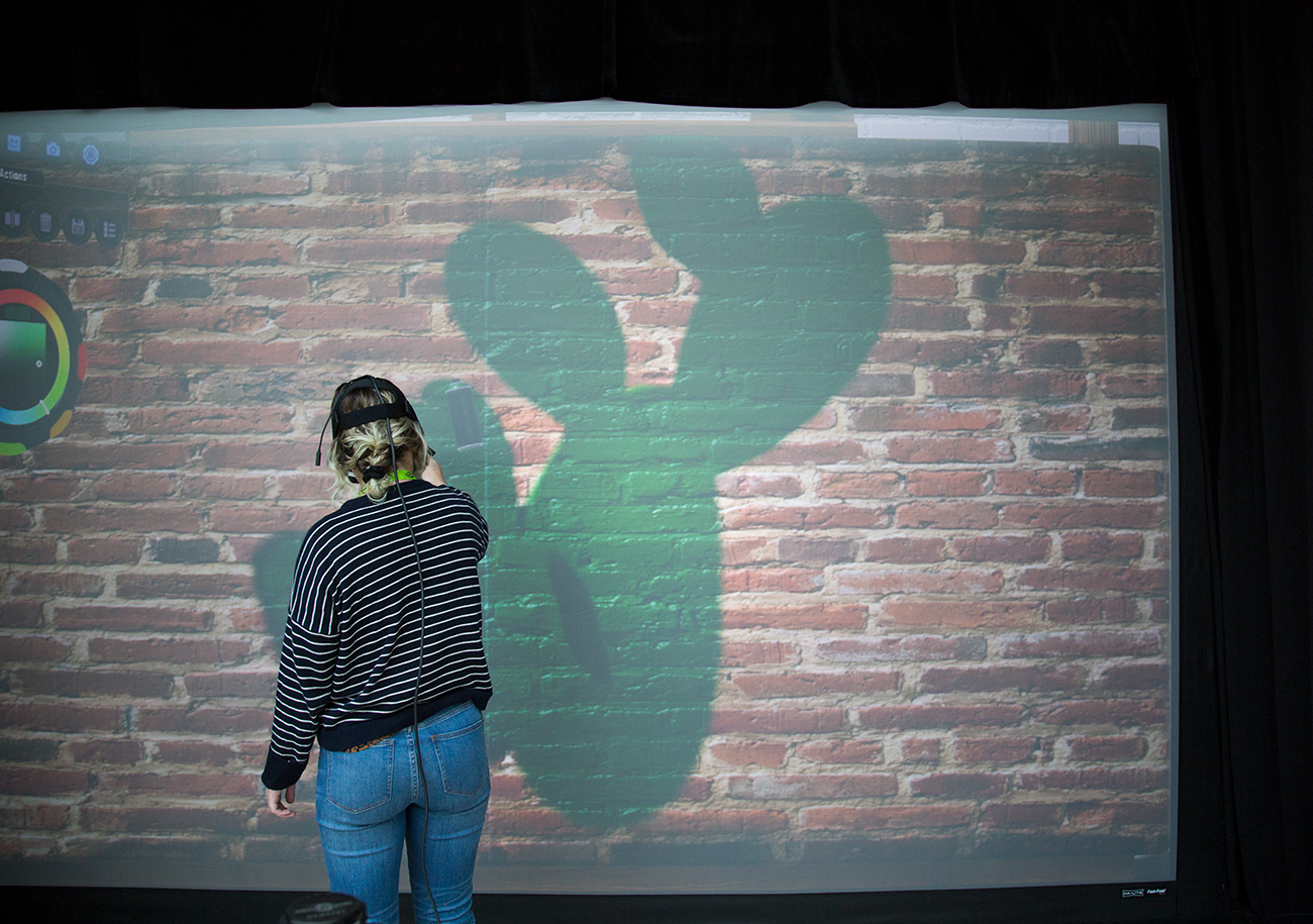 A woman wearing a virtual reality headset digitally spray painting a green cactus on a digital brick wall.