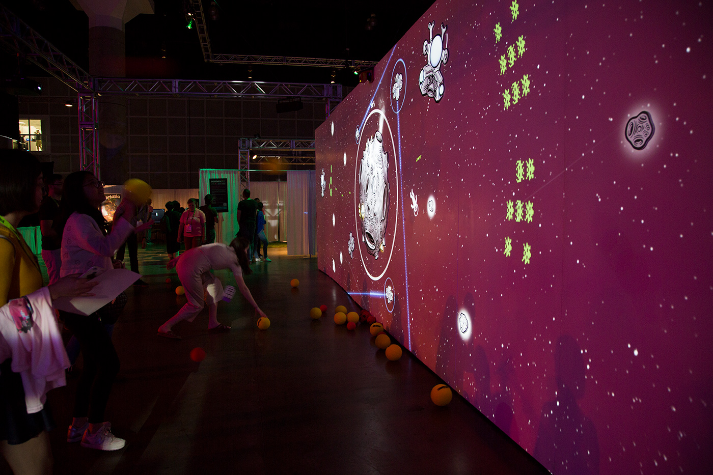 People throwing foam balls at big wall with a projected game featuring aliens and astronauts.