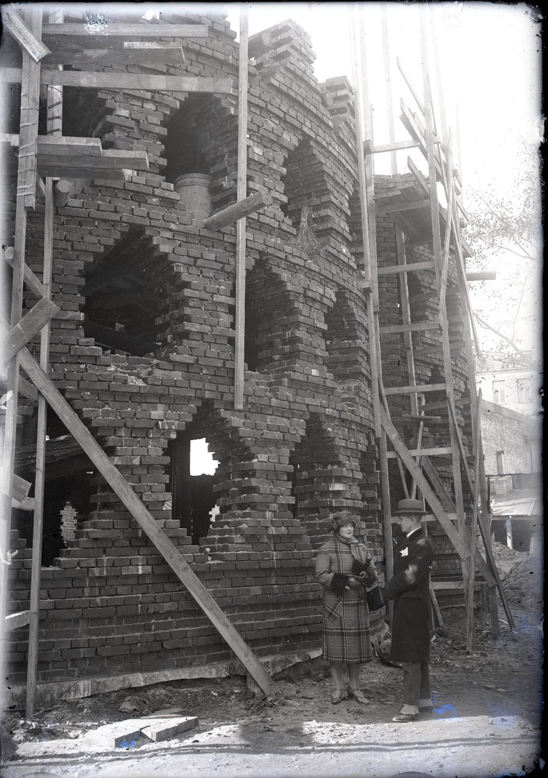 Black and white photograph of a cylindrical brick structure with hexagonal windows under scaffolding, being constructed