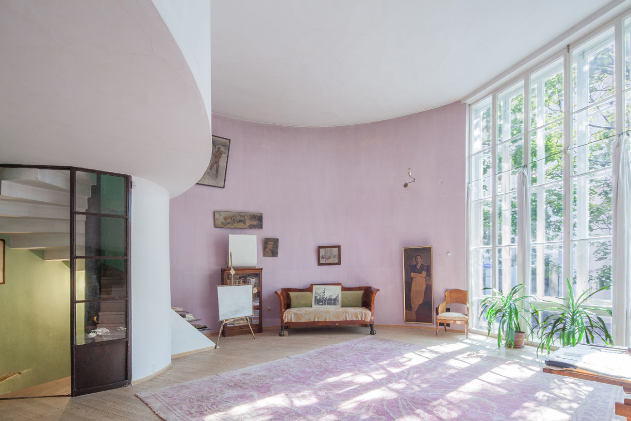Interior of a cylindrical house showing a pink curved wall and floor-to-ceiling windows