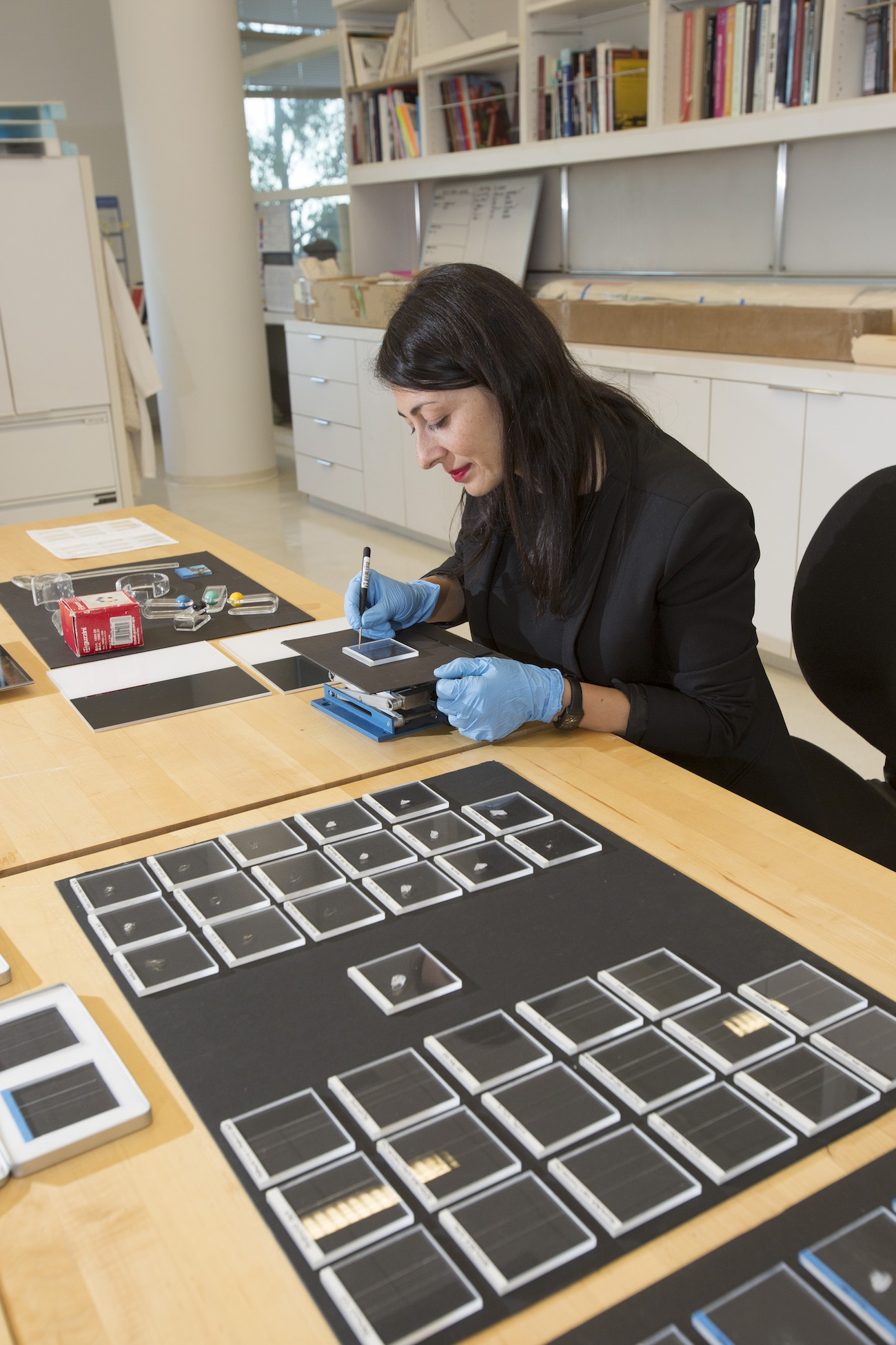 A woman with brown hair sits at a work table, working on plastics samples wearing blue gloves