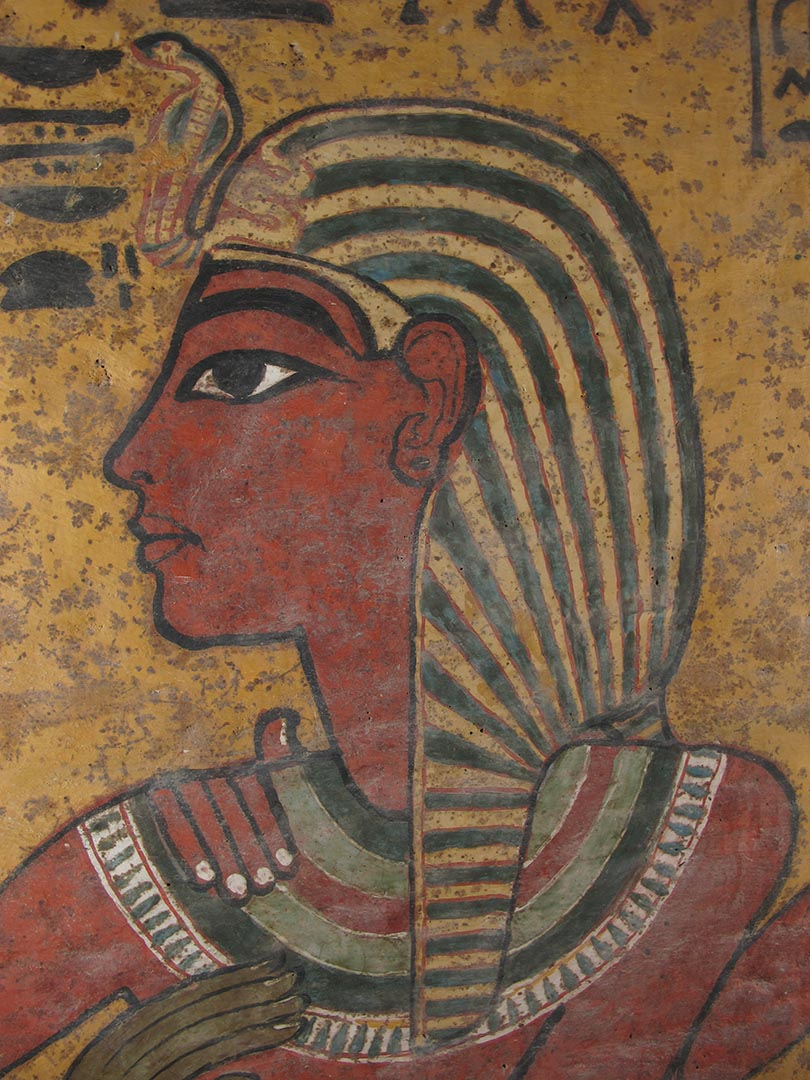 Side view of Tutankhamen wearing a striped headdress with a snake