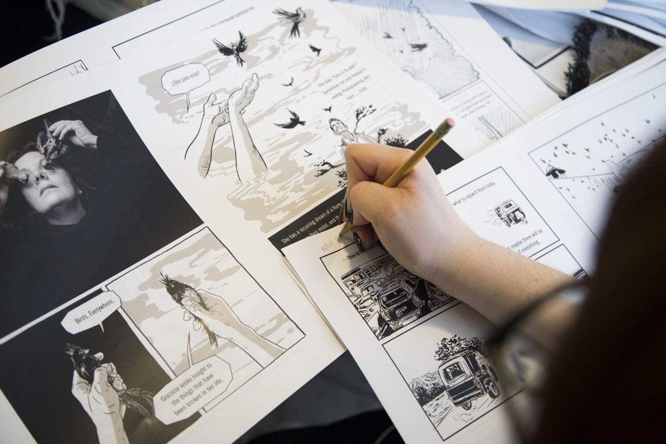 A hand holding a pencil makes notes (not legible) on comic book panels depicting hands holding birds.