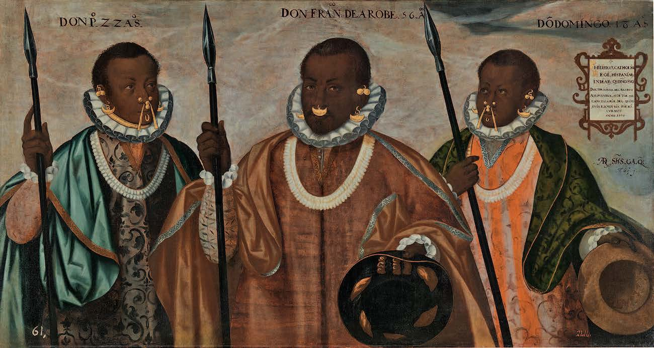 Three men with dark skin stand carrying spears and wearing nose and ear ornaments and colorful robes