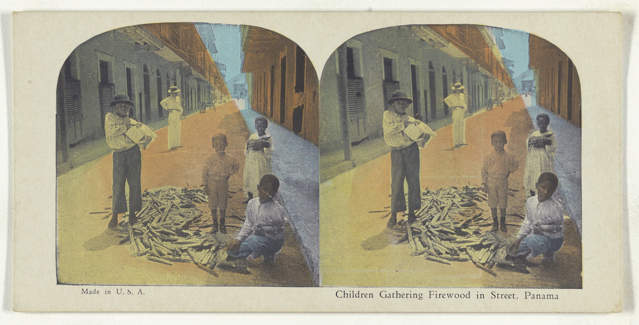 Stereograph (double image) with painted color of children in a deserted street gathered around a small pile of firewood
