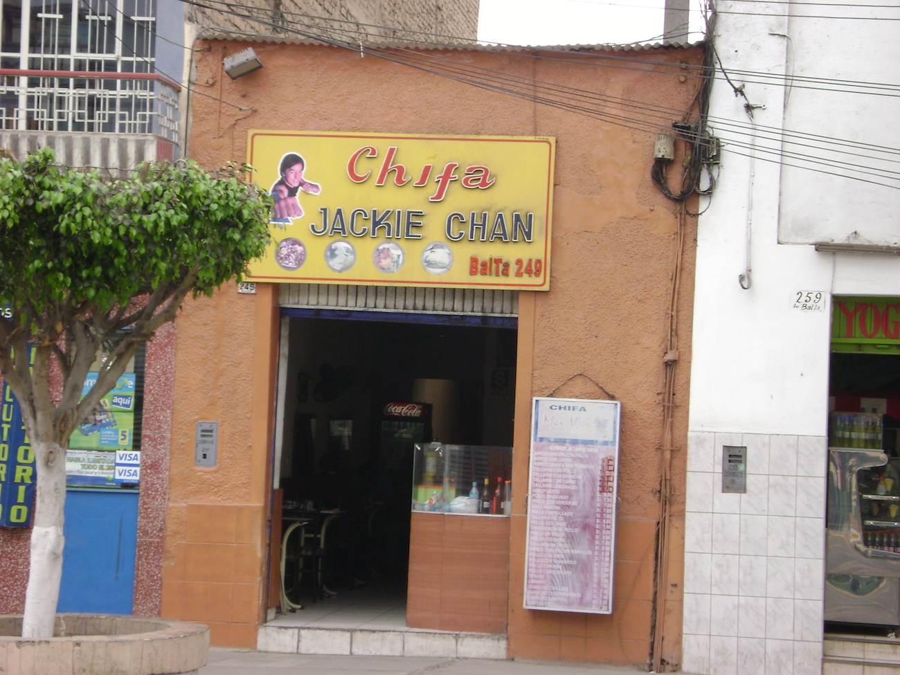 "Exterior of a modest restaurant with stucco walls and a bright yellow and red sign reading ""chifa"""