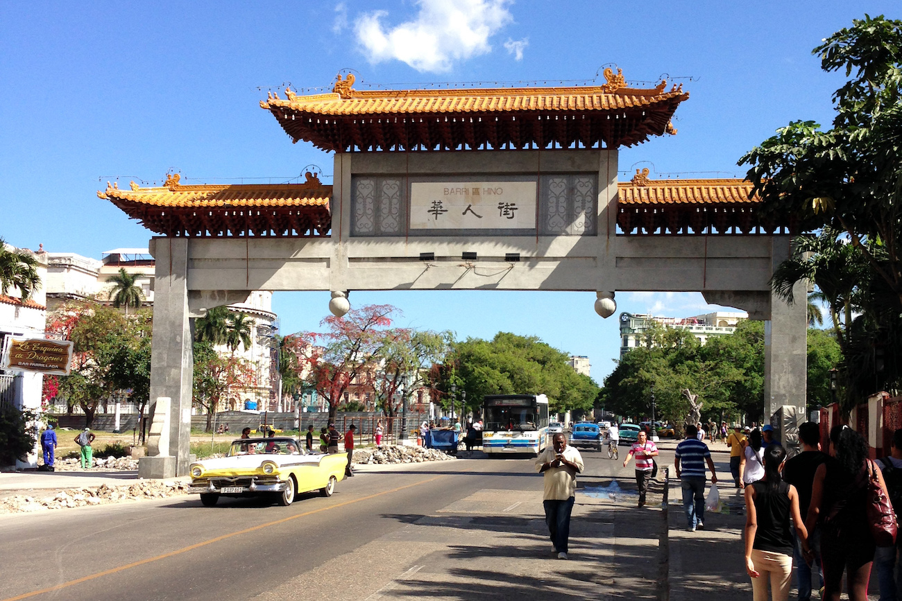 Color photo of a Chinese-style concrete gate spanning a two-lane public street in Havana