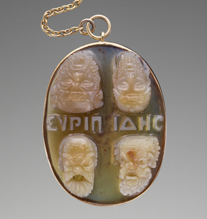 A carved gem on a gold chain showing a grid of four theatrical masks and the word Euripides in Greek letters