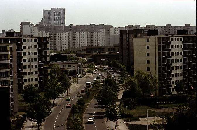 Color photo of tall apartment blocks towering over a street in West Berlin