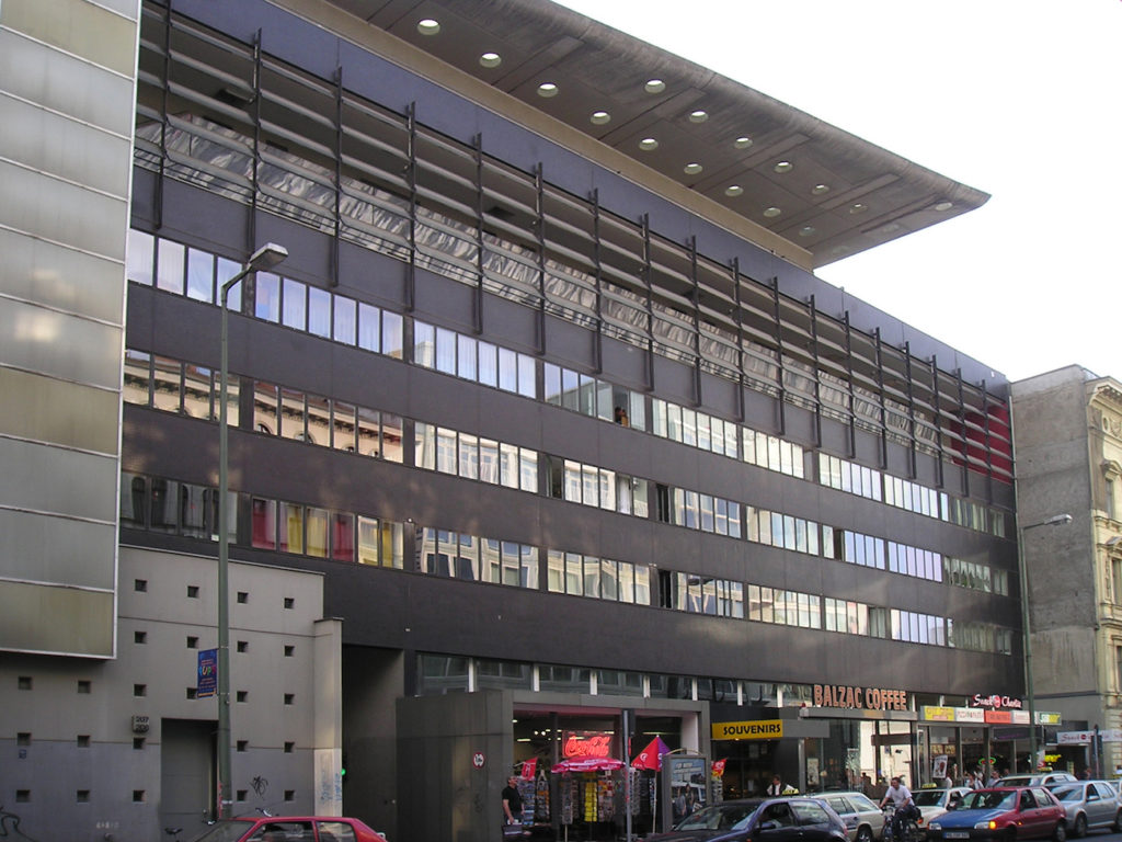Color photo of a metal-and-glass modernist apartment building with stores on the ground floor