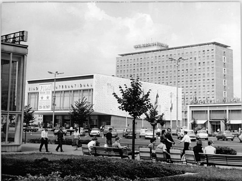 Black and white building showing three 1960s buildings in East Berlin. In the foreground, pedestrians and people on benches