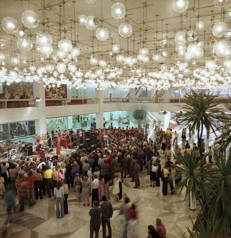 Color photo of young adults in a large, grand foyer of a municipal building. The space has high ceilings and is lit by multiple globe-shaped lamps