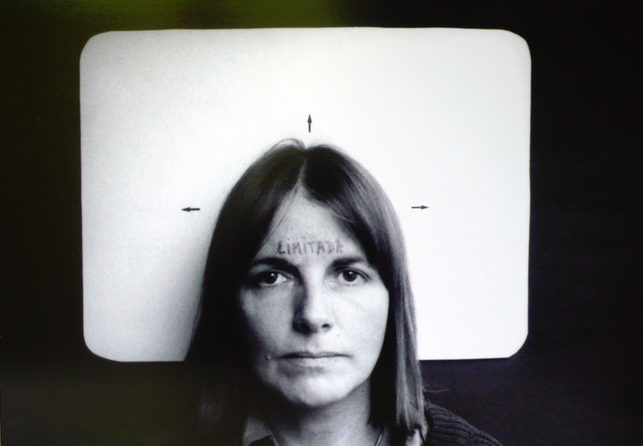 Black and white photo of a woman with straight hair staring at the viewer. She has the word LIMITADA written on her forehead